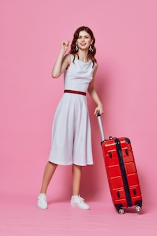 Mulher com mala vermelha vestido branco emoções viajar fundo rosa