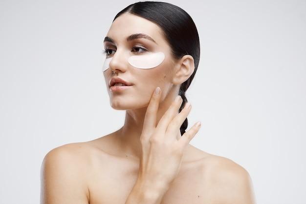 Mulher com manchas nos ombros nus perto de cosméticos para os olhos