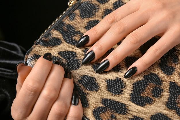 Mulher com manicure profissional segurando bolsa de couro, close-up