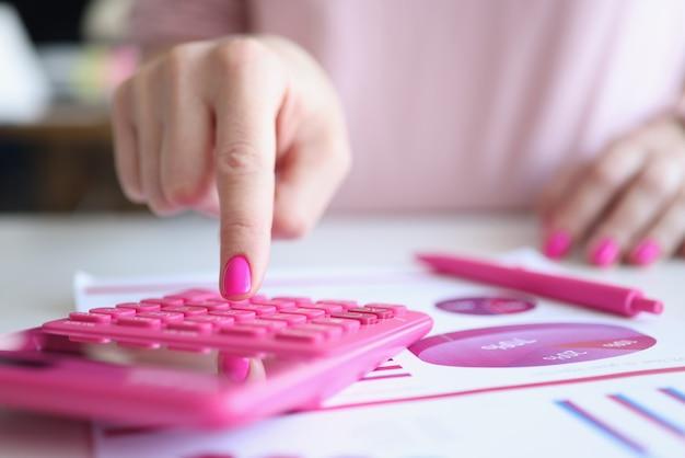 Mulher com manicure rosa contando na calculadora perto do papel com gráficos close
