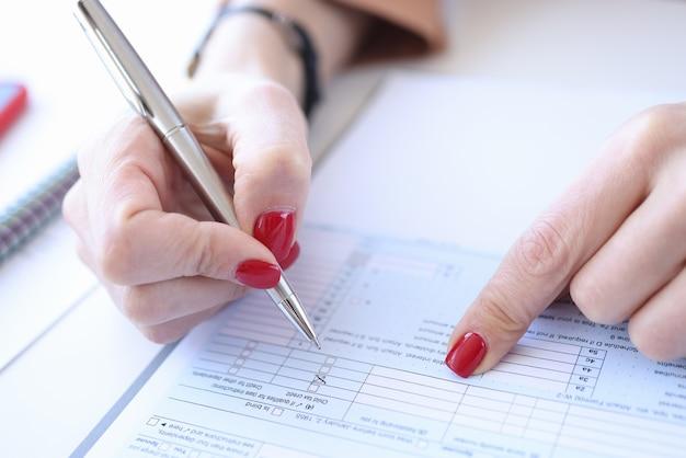 Mulher com manicure vermelha preenchendo questionário close up