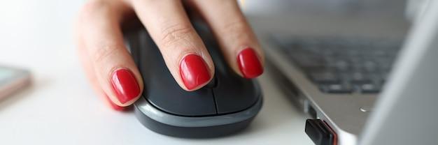 Mulher com manicure vermelha segurando o mouse do computador perto do laptop, close-up
