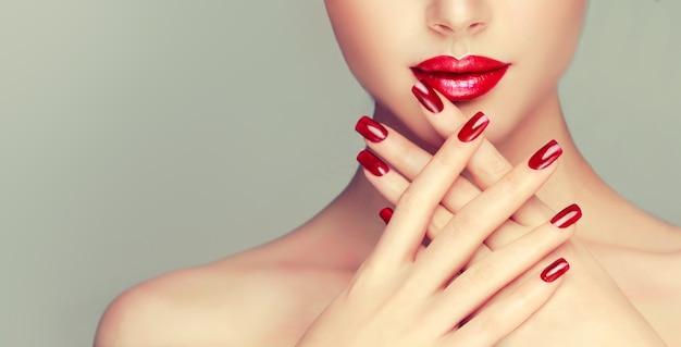 Mulher com manicure vermelho brilhante nas unhas e lábios vermelhos bem formados