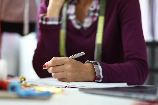 Mulher com manicure vermelho segura a caneta.