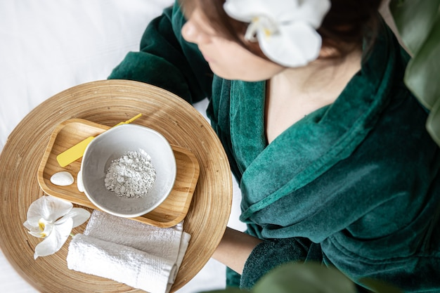 Mulher com manto verde, segurando o prato com máscara de argila e flor de orquídea, vista superior, conceito de tratamentos de spa.
