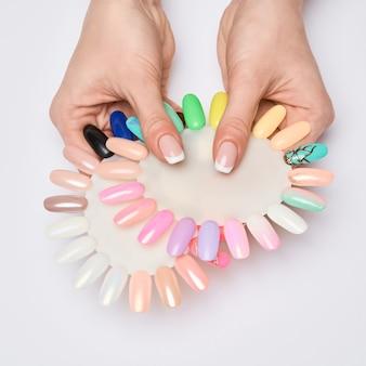 Mulher com mãos bem cuidadas e unhas saudáveis, segurando uma paleta com coleção de amostras de esmalte para manicure.