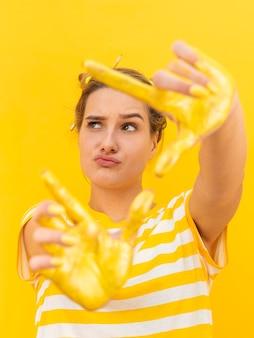 Mulher com mãos pintadas amarelas