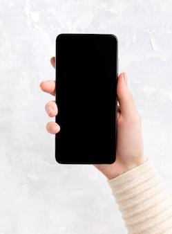 Mulher com mãos preparadas com design de unhas rosa bege nude, segurando o smartphone. modelo de escritório comercial