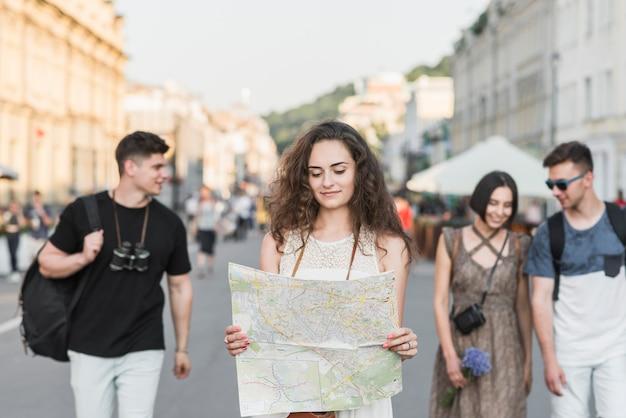 Mulher, com, mapa, andar, com, amigos, rua