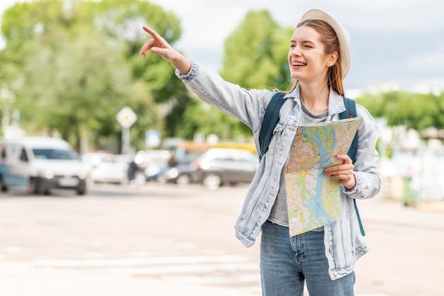 Mulher com mapa apontando o dedo no ar