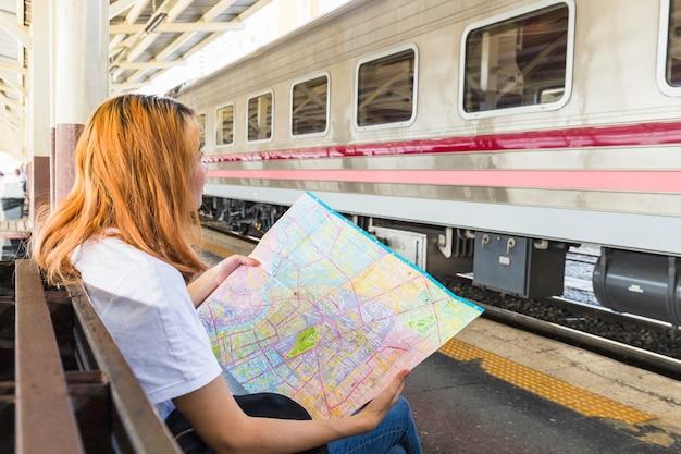 Mulher, com, mapa, ligado, assento, ligado, plataforma