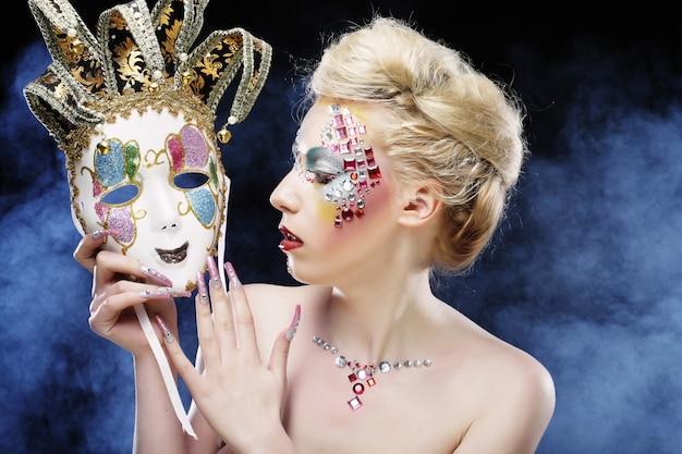 Mulher com maquiagem artística segurando a máscara