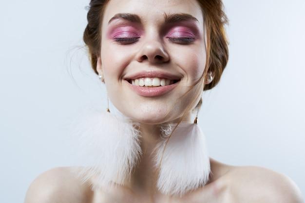 Mulher com maquiagem brilhante, brincos fofos, ombros nus, close-up