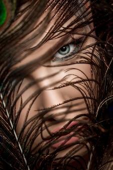 Mulher com maquiagem brilhante e penas de pavão
