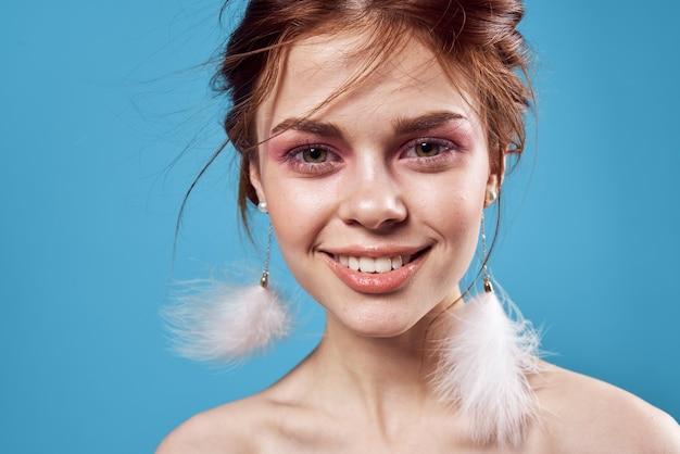 Mulher com maquiagem brilhante no rosto de ombros nus fundo azul de luxo.