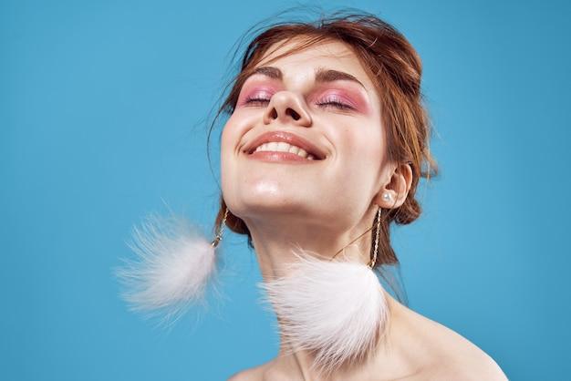Mulher com maquiagem brilhante no rosto ombros nus fundo azul de luxo.