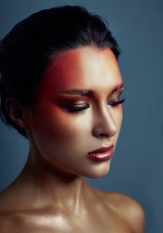 Mulher com maquiagem brilhante vermelha no rosto e olhos