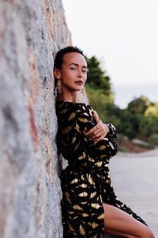 Mulher com maquiagem bronze em vestido preto dourado na parede de pedra