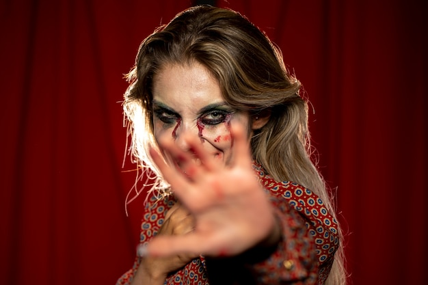 Mulher com maquiagem como sangue e mão na frente dela