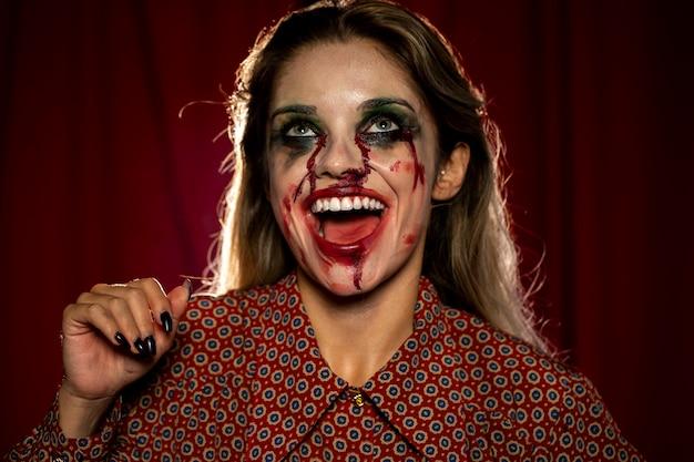 Mulher com maquiagem como sangue rindo