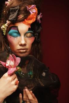 Mulher com maquiagem criativa segurando flor rosa