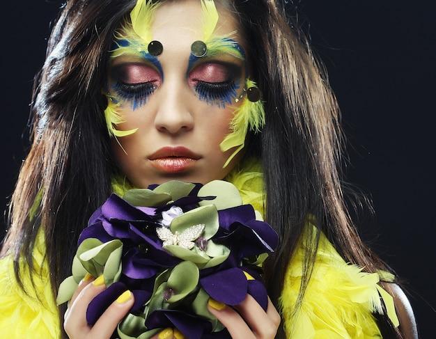 Mulher com maquiagem criativa segurando um buquê de jóias