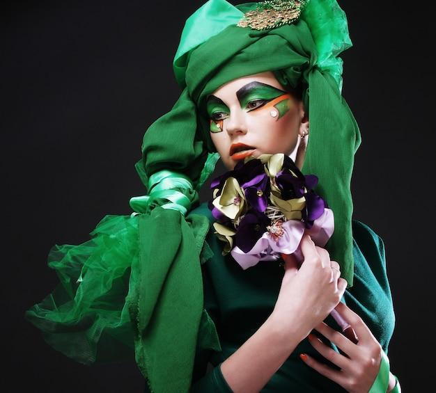 Mulher com maquiagem criativa segurando um buquê