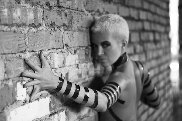 Mulher com maquiagem criativa. zumbi cibernético feminino. edifício destruído.