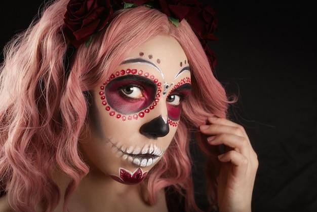 Mulher com maquiagem de caveira de açúcar e cabelo rosa isolado