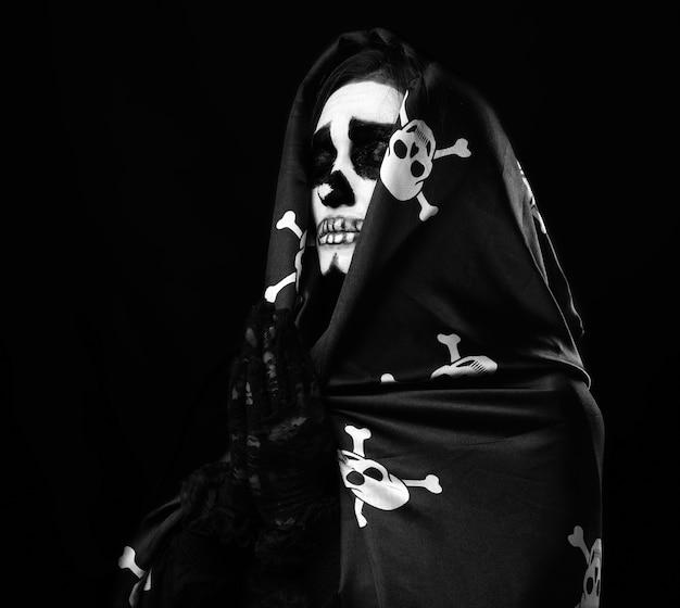 Mulher com maquiagem de esqueleto em pose de oração