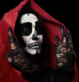 Mulher com maquiagem de esqueleto em uma capa vermelha