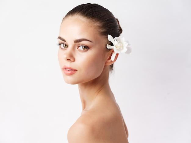 Mulher com maquiagem de flores no cabelo e ombros nus