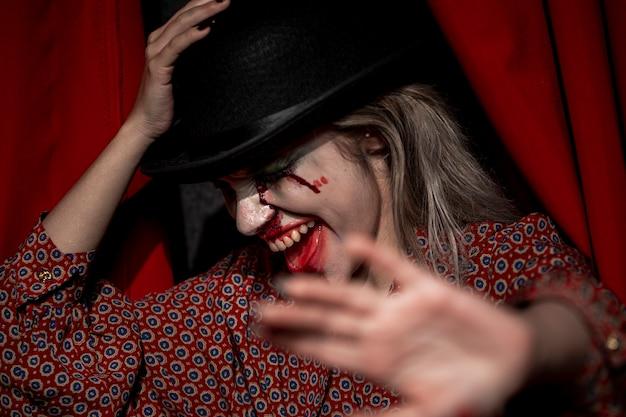 Mulher com maquiagem de palhaço de halloween, escondendo o rosto