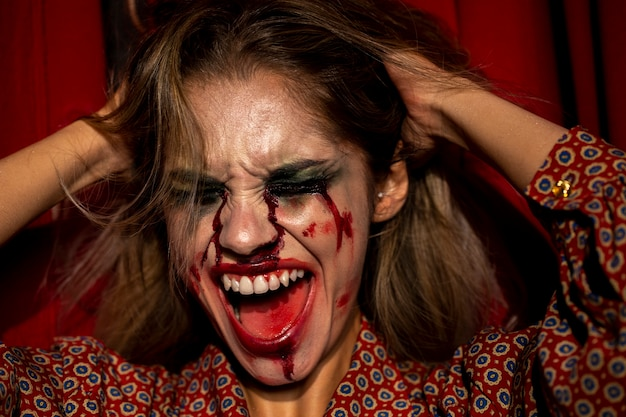 Mulher com maquiagem de palhaço de halloween gritando