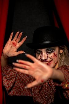 Mulher com maquiagem de palhaço de halloween, olhando para a câmera e se escondendo