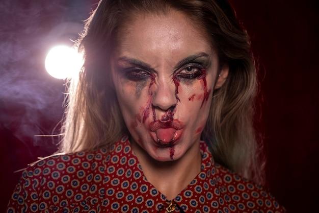 Mulher com maquiagem de palhaço de halloween saindo da língua para fora