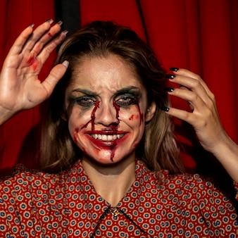Mulher com maquiagem de palhaço de halloween sorrir com os dentes