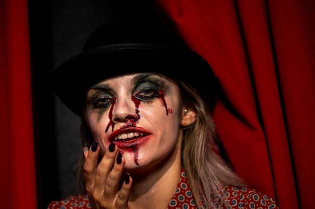 Mulher com maquiagem de sangue de palhaço de halloween