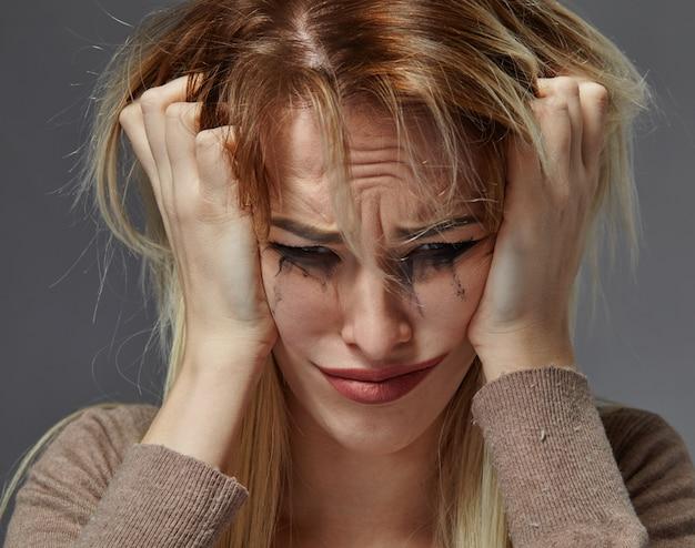 Mulher com maquiagem desbotada e segurando as mãos na cabeça