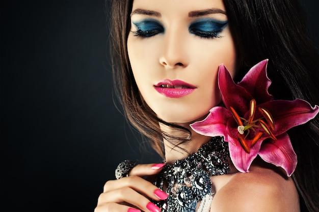 Mulher com maquiagem e flor. maquilhagem para sombras azuis, lábios rosados