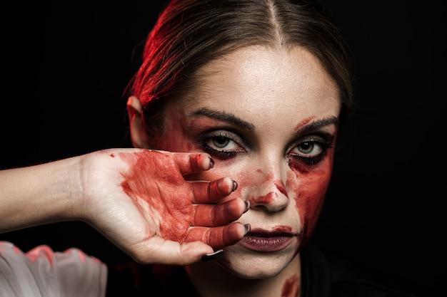 Mulher com maquiagem e mão ensanguentada