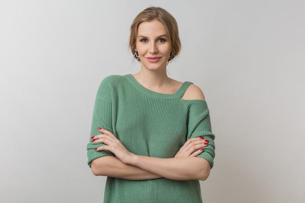 Mulher com maquiagem elegante e suéter verde posando em rosa