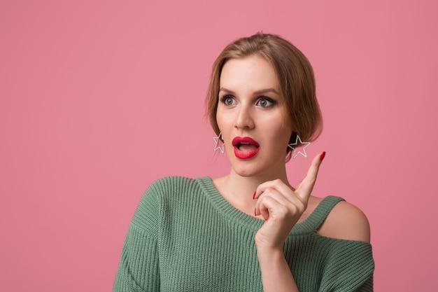 Mulher com maquiagem elegante, lábios vermelhos, suéter verde posando em rosa