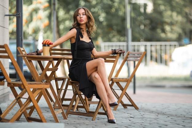 Mulher com maquiagem em um vestido preto elegante em um café de verão