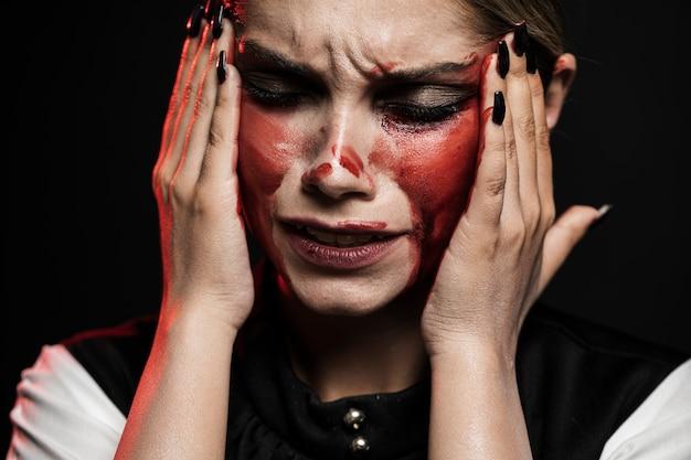 Mulher com maquiagem ensanguentada, segurando sua cabeça