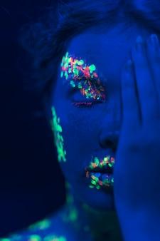 Mulher com maquiagem fluorescente e mão no rosto