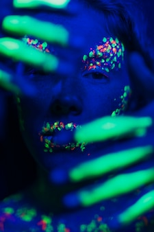Mulher com maquiagem fluorescente no rosto e mãos