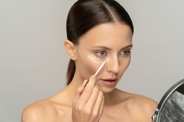 Mulher com maquiagem natural, aplicando corretivo na pele impecável e fresca, fazendo maquiagem olhando no espelho