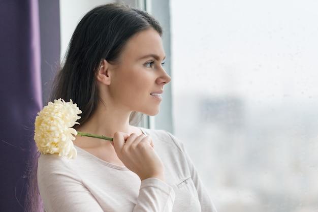 Mulher com maquiagem natural, com grande flor amarela pálida