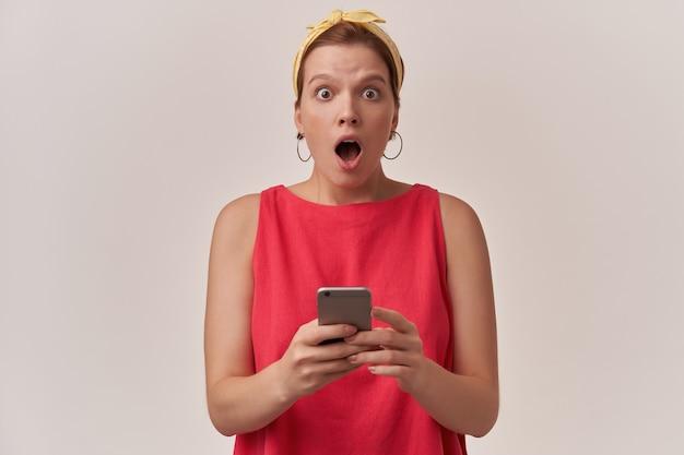 Mulher com maquiagem natural e brincos usando um vestido vermelho da moda elegante e bandana amarela posando